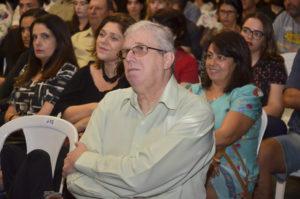 Foto de homem grisalho, de camisa clara, braços cruzados e de óculos, numa plateia