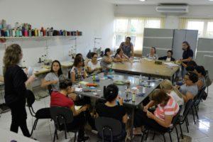 Pessoas sentadas ao redor da mesa que tem materiais para oficina