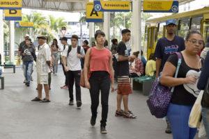 Foto de pessoas andando por um terminal de ônibus
