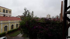 Foto do céu com muitas nuvens e edificações e vegetação de parte do Complexo Argos