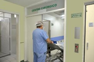 Médico entrando com maca em porta aberta do Centro Cirúrgico do Hospital São Vicente
