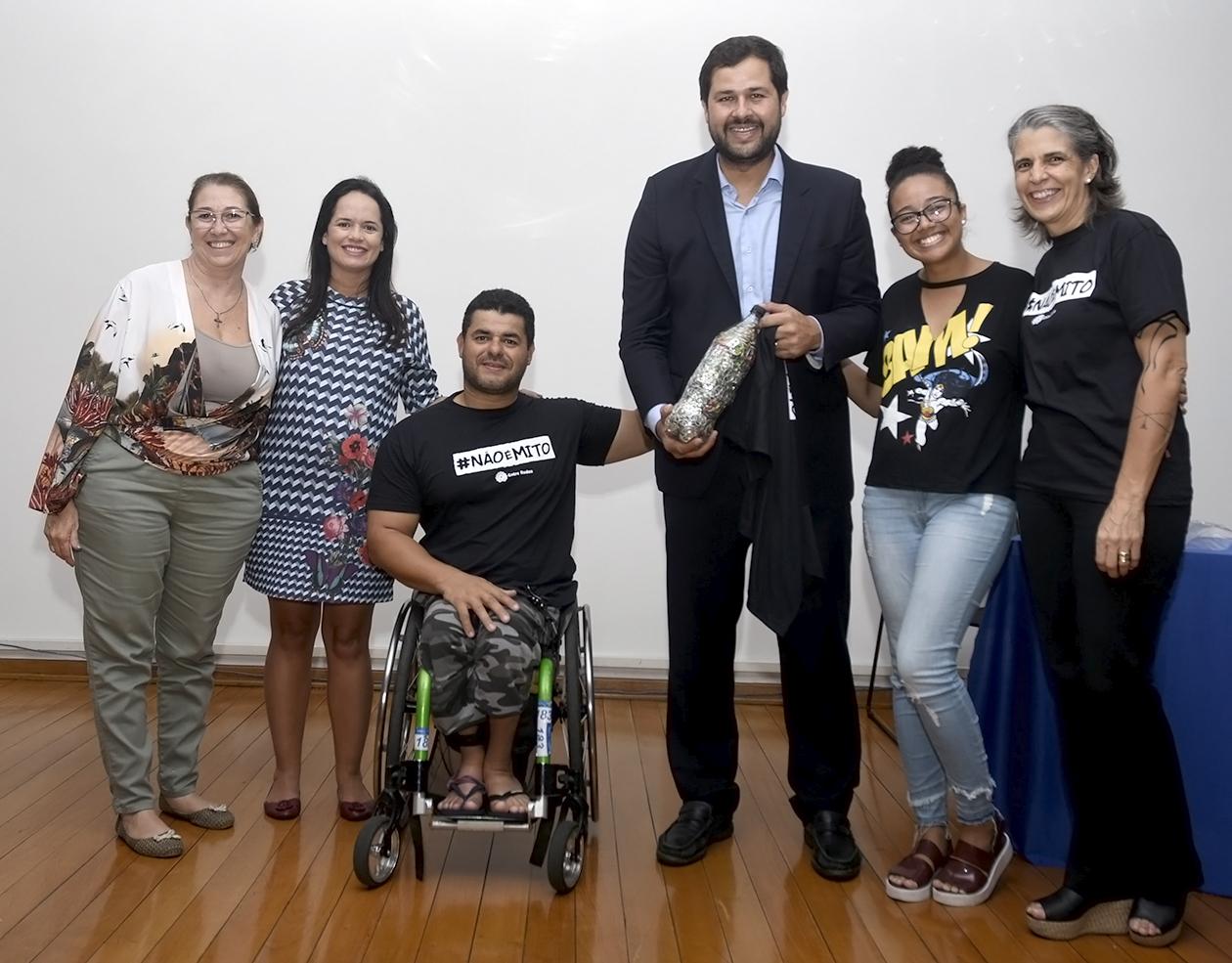 cadeirante recebe garrafa com lacres de latas de alumínio, utilizados para confeccionar cadeiras de roda
